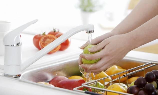 Женщина моет фрукты и овощи